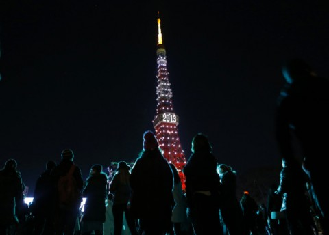 People look at  the Tokyo Tower which is illuminated to celebrate the New Year at a countdown event in Tokyo